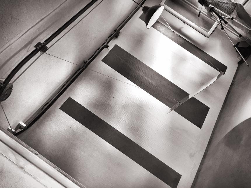 Ein gekippter Raum, die Wand des Raumes ist weiß und drei unterschiedlich breite schwarze Streifen. Ein Spiegel hängt kaum sichtbar in der Mitte des Raumes, an Kabeln befestigt, die von der Decke hängen. Eine Lampe beleuchtet den Spiegel. Das Bild ist schwarz/weiß.