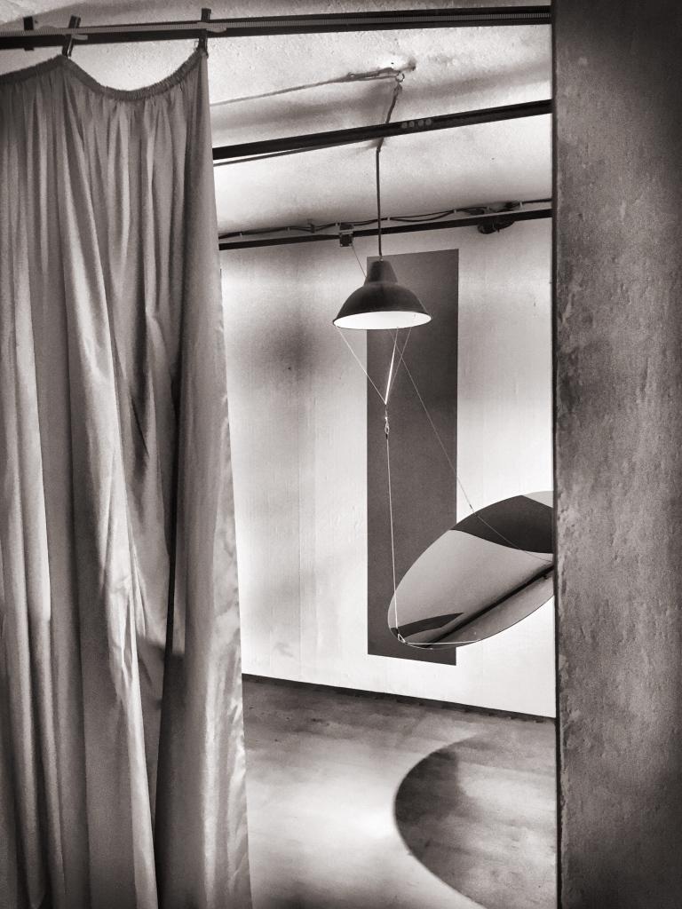 Ein Spiegel hängt in der Mitte eines Raumes. Rechts begrenzt eine Wand den Blick in den Raum mit dem Spiegel. Links begrenzt ein Vorhang den Blick. Eine Lampe hängt von der Zimmerdecke und beleuchtet den Spiegel. Das Bild ist schwarz/weiß.