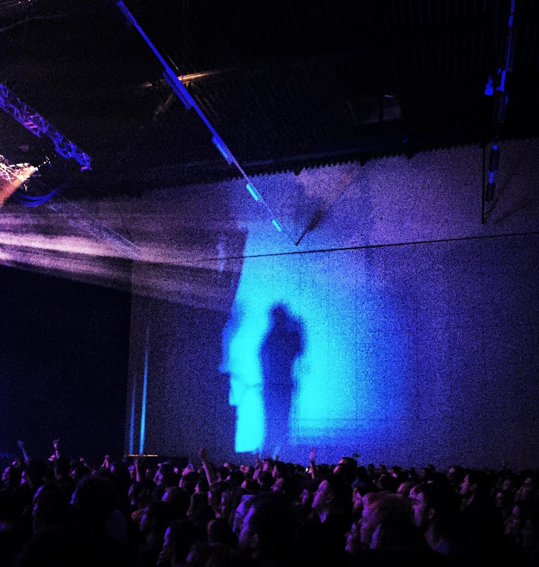 Ein Schatten einer Person in blauem Licht an einer Wand, darunter die Köpfe vieler Menschen.