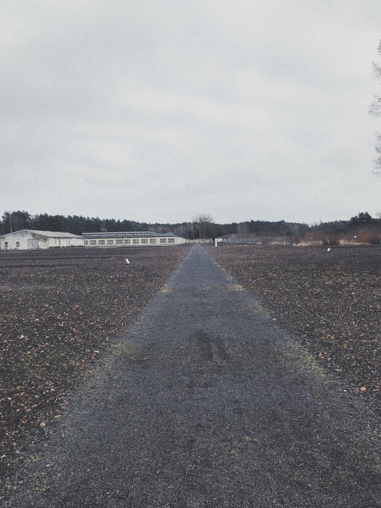 Weg, links und rechts liegen Schottersteine, am Ende des Weges stehen flache Häuser.