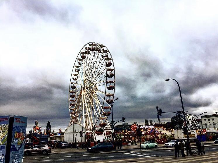 Ein Riesenrad auf einem Jahrmarkt, der Himmel drückt mit dunklen Wolken auf die Stimmung. Autos fahren vorbei.