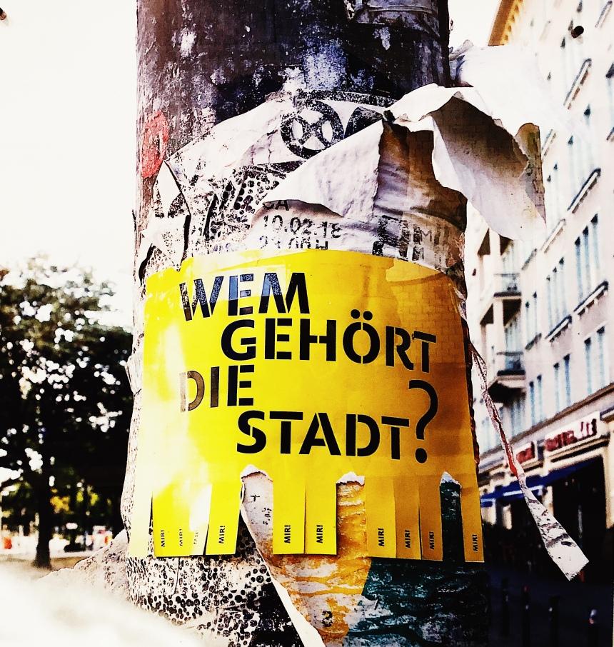 """Ein Ausschnitt eines Laternenpfahls mit den Überresten von vielen Plakaten. Auf den Überresten klebt ein gelbes Plakat mit der Aufschrift """"Wem gehört die Stadt?"""""""