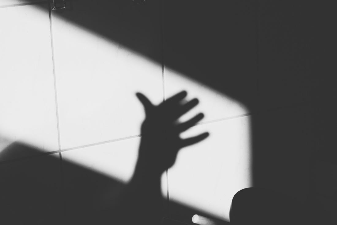 Schwarz-weiß Bild, Schatten einer Hand auf Fliesen.