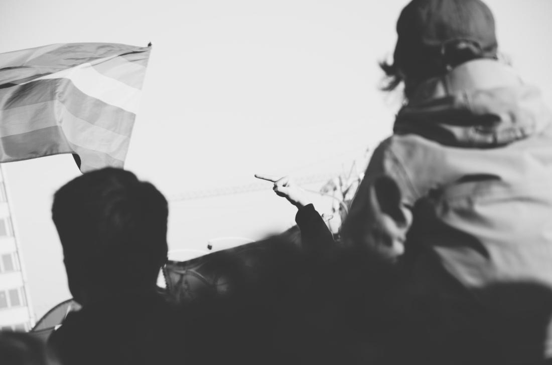 Eine unscharfe Menschenmenge im Vordergrund. Links wird eine Fahne geschwungen. Im Zentrum des Bildes zeigt jemand seinen Mittelfinger.
