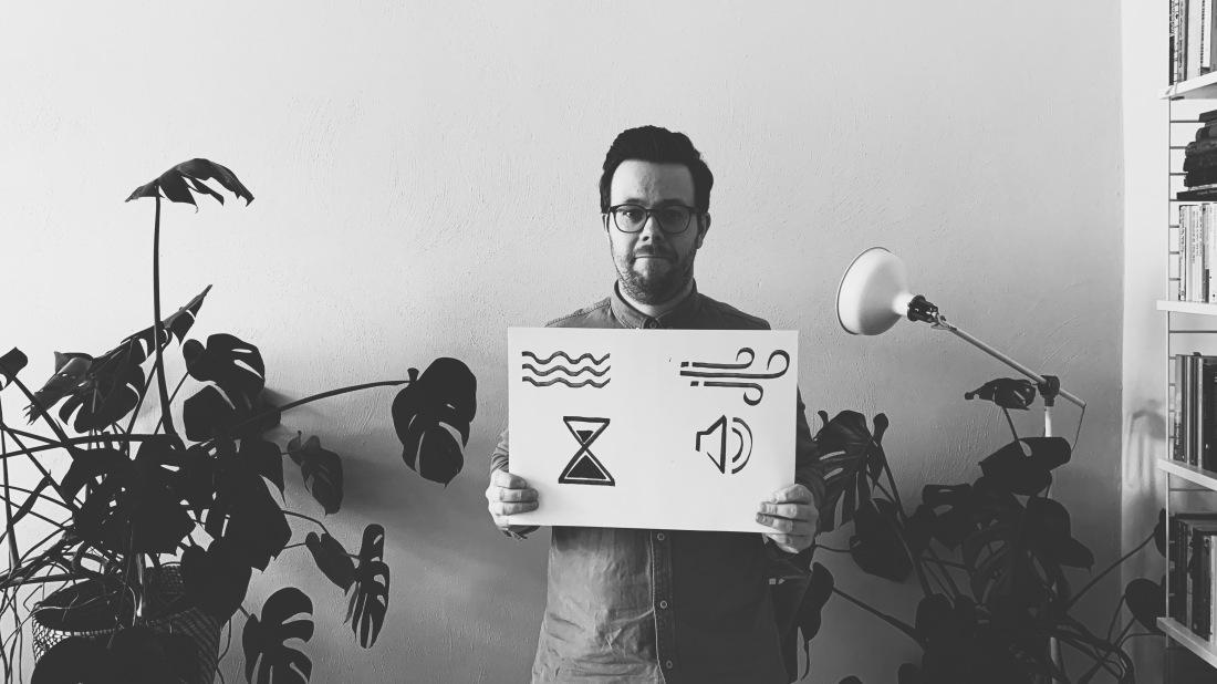 Schwarz-weiß Bild, ein Mann mit Brille hält ein Plakat auf dem ein Wellensymbol, ein Sturmsymbol, eine Sanduhr und ein Lautsprechersymbol zu sehen sind.