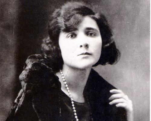 Schwarz/weiß-Foto von Florbela Espanca. Sie trägt eine Perlenkette und einen Mantel mit Fellkragen.