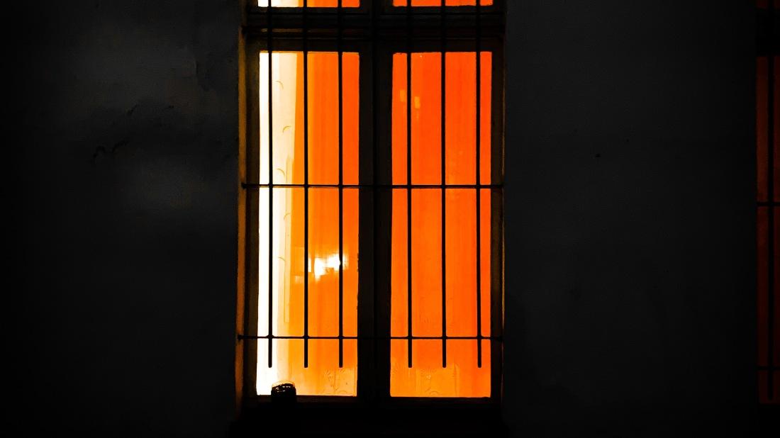 hell erleuchtetes Fenster mit Gittern davor