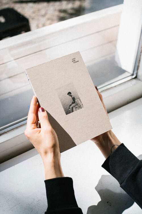 Zwei Hände halten das Buch Lost And Found vor einem Fenster in der Hand. Auf dem Cover des Buches ist ein Bild zu erkennen, darauf sitzt eine Frau auf einem Steg am Wasser.