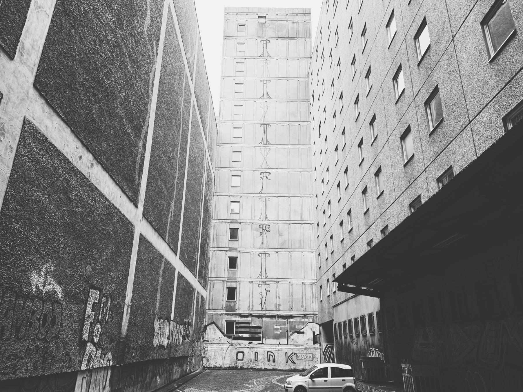 Schwarz-weiß Bild, Hinterhof mit drei unterschiedlichen Plattenbauwänden, links ohne Fenster. In der Mitte des Hofes steht ein Auto, Graffitis sind auf den Wänden zu sehen.