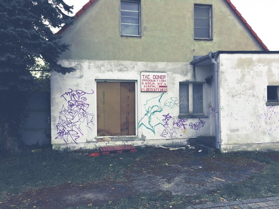 """Altes, zweigeschossiges Haus mit flachem Anbau. Die Eingangstür fehlt und ist mit Spanplatten zugebaut. Das Sockelgeschoss ist weiß getüncht. Zwischen dem Fenster und der Eingangstür hängt ein Schild mit der Aufschrift """"Tag Döner - Produktion""""."""