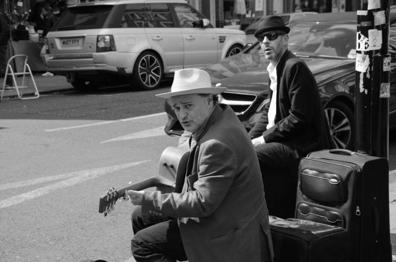 schwarz-weiß Bild, zwei Musiker sitzen an einer Straße, einer trägt einen weißen Hut mit Krempe, er spielt Gitarre und schaut skeptisch ins Bild. Der andere Musiker schaut aus dem Hintergrund ins Bild, erträgt einen schwarzen Hüten und Sonnenbrille. Zwischen den Musikern steht ein Koffer und ein Verstärker