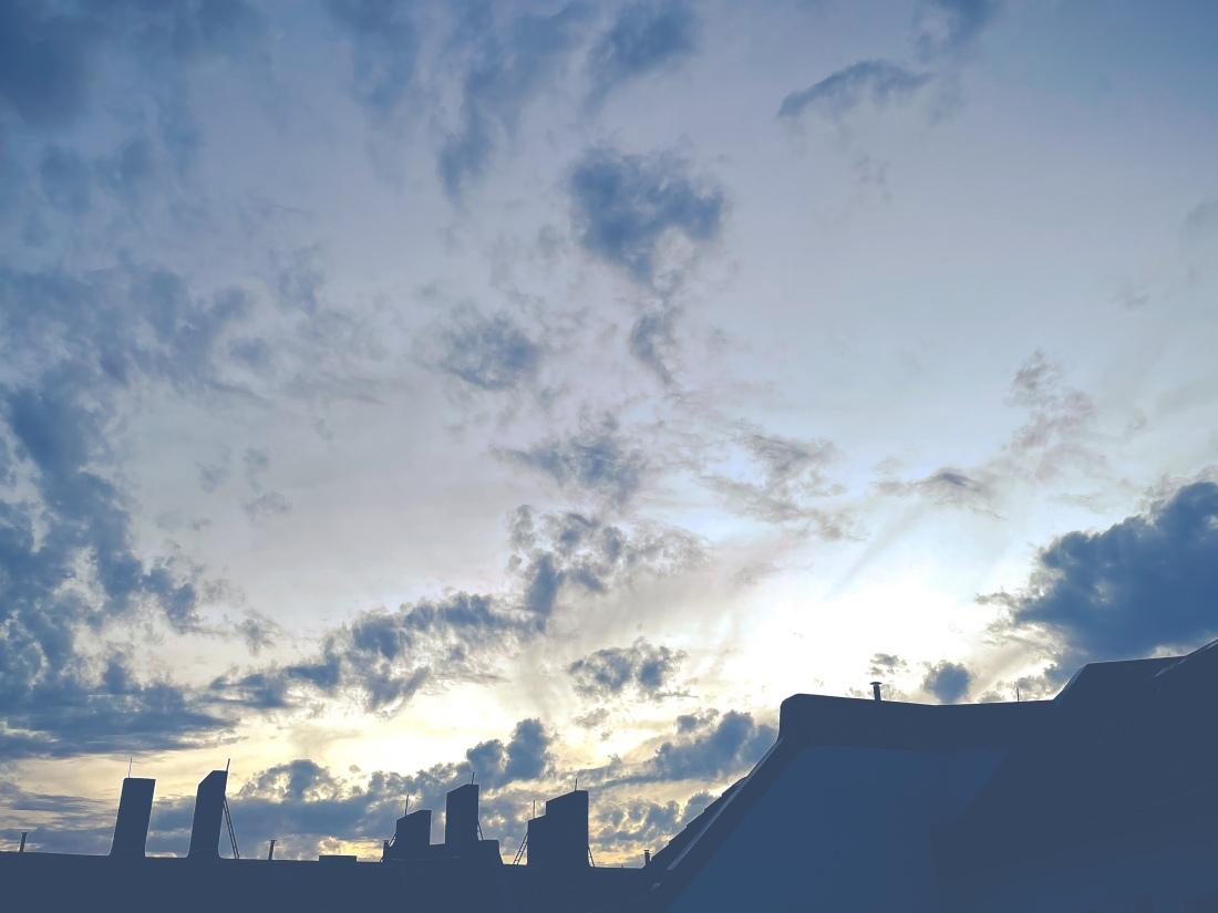 Sonnenuntergang hinter einem Haus, von dem nur Teile des Dachs und einzelne Schornsteine zu sehen sind