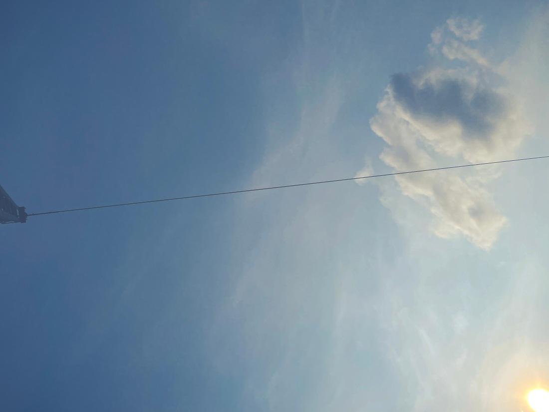 Blauer Himmel, eine Wolke auf der rechten Bildseite, die Sonne in der unteren, rechten Ecke, eine Oberleitung zieht durchs Bild