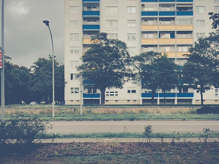 Im Vordergrund läuft eine Straße von rechts nach links. Ein Plattenbau steht im Hintergrund. Die verschieden farbigen Balkonbrüstungen sind blau und gelb. Eine Laterne steht links vor dem Haus.