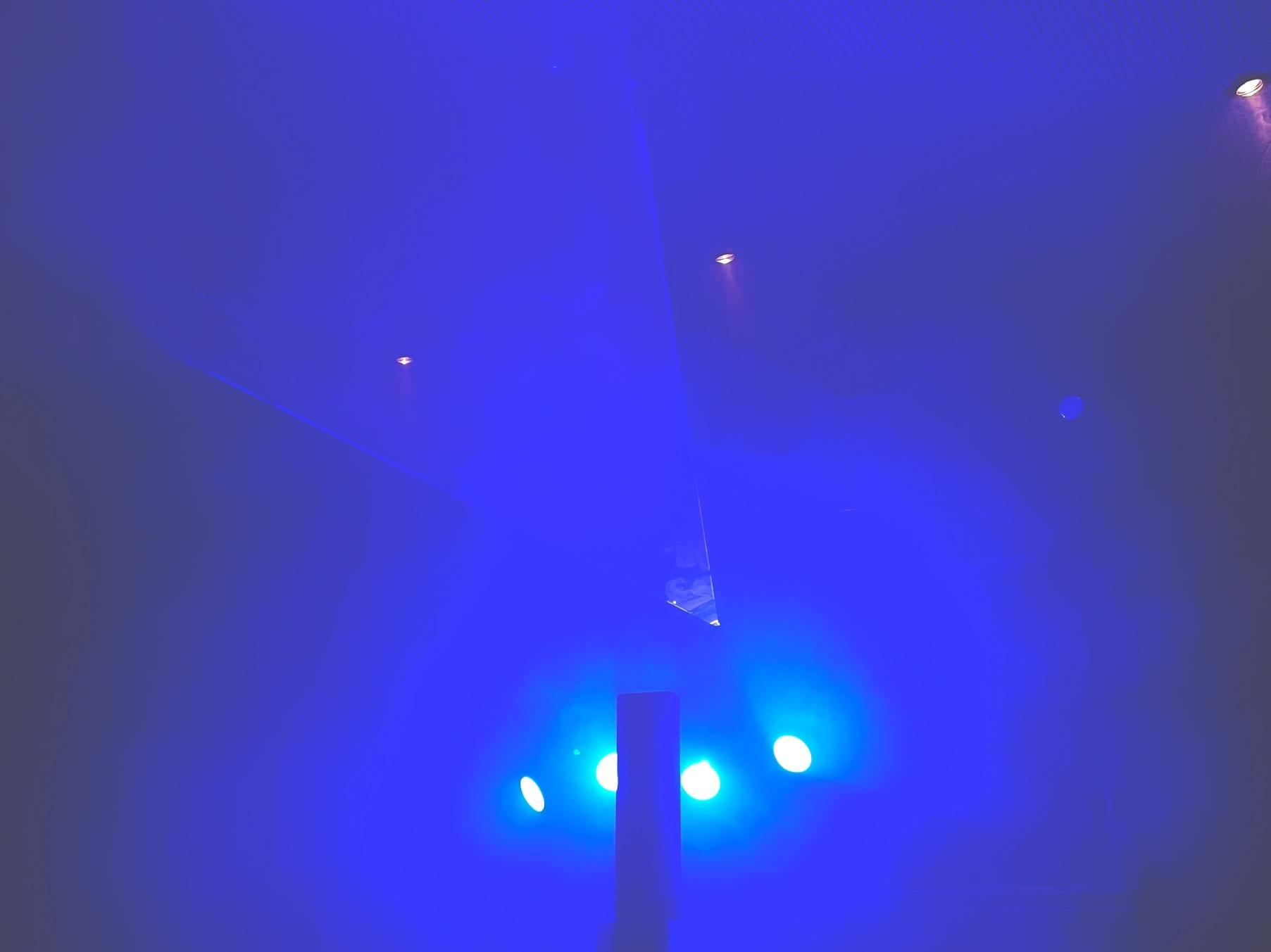 vier blaue Lichter leuchten wie Scheinwerfer in einen nebligen Raum, eine Säule steht vor den Lichtern