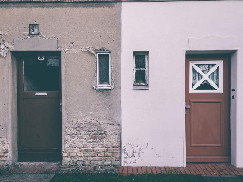 Gebäude mit zwei Türen, eine Hälfte des Gebäudes ist renoviert worden, die andere nicht, Putz bröckelt von den Wänden.